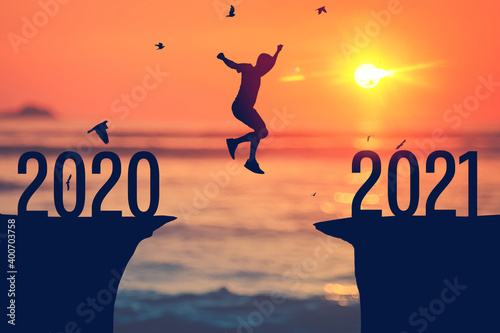 Fototapeta Silhouette man jumping between cliff with number 2020 to 2021 at tropical sunset beach. Freedom challenge and travel adventure holiday concept. obraz