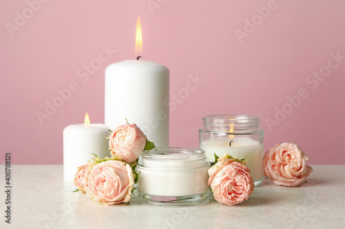 Fototapeta Scented candles and roses on white table against pink background obraz