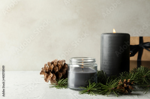 Obraz Scented candles, gift box and pine branches with cones on white table - fototapety do salonu