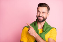 Photo Of Charming Young Man Dressed Yellow T-shirt Sweater Shoulders Pointing Looking Empty Space Isolated Pink Color Background