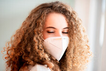 Young Curly Hair Woman Wearing A Medical Face Mask And Closing Eyes, Close-up Portrait Of A Face Isolated On A White Background