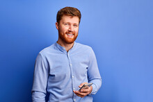 Optimistic Male Is Chatting With Friend On Mobile Phone, Typing Message, Wearing Blue Formal Shirt, Smiling. Isolated On Blue Background
