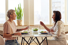 Smiling Couple Enjoying Dinner Meal Sitting At Kitchen Table Together And Drinking White Wine Healthy Eating