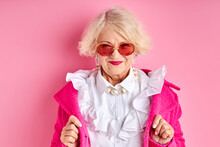 Fancy Aged Lady In Eyeglasses Posing At Camera Wearing Fashionable Clothes, Isolated Over Pink Background