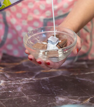 Woman Pouring Milk Into Pieces Of Chocolate Over A Glass Bowl