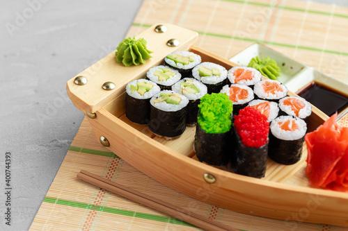 Fototapeta Set of maki sushi on wooden boat tray obraz
