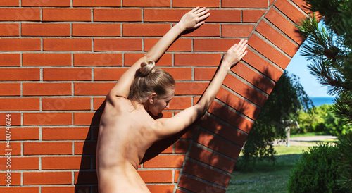 Fototapeta Nude woman near a brick wall