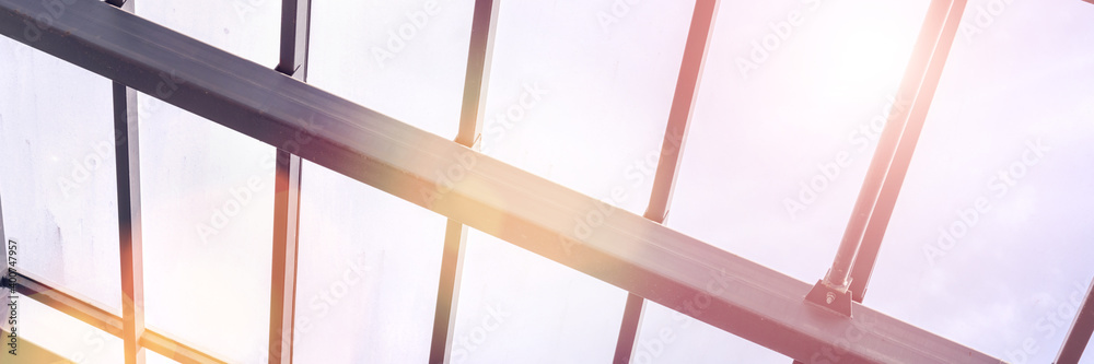 Fototapeta Metal roof building construction with transparent glass material under rays of sun