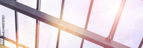 Fototapeta Metal roof building construction with transparent glass material under rays of sun obraz