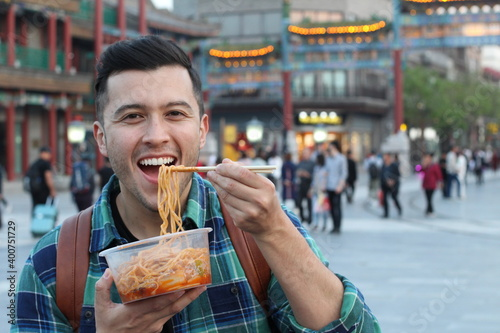 Obraz Man enjoying Asian street food  - fototapety do salonu