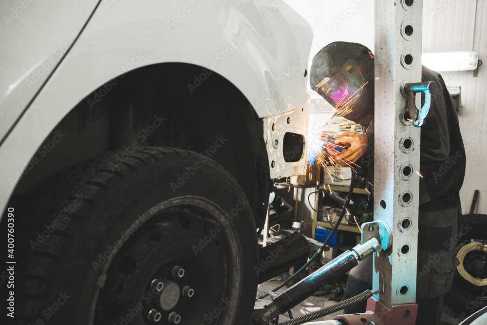 Fototapeta Industrial worker at car service welds automotive body. Metalworking with carbon dioxide welding.
