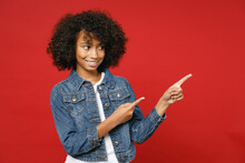Pretty Little African American Kid Girl 12-13 Years Old In Casual Denim Jacket Pointing Index Fingers Aside Up Isolated On Bright Red Background Children Studio Portrait. Childhood Lifestyle Concept.