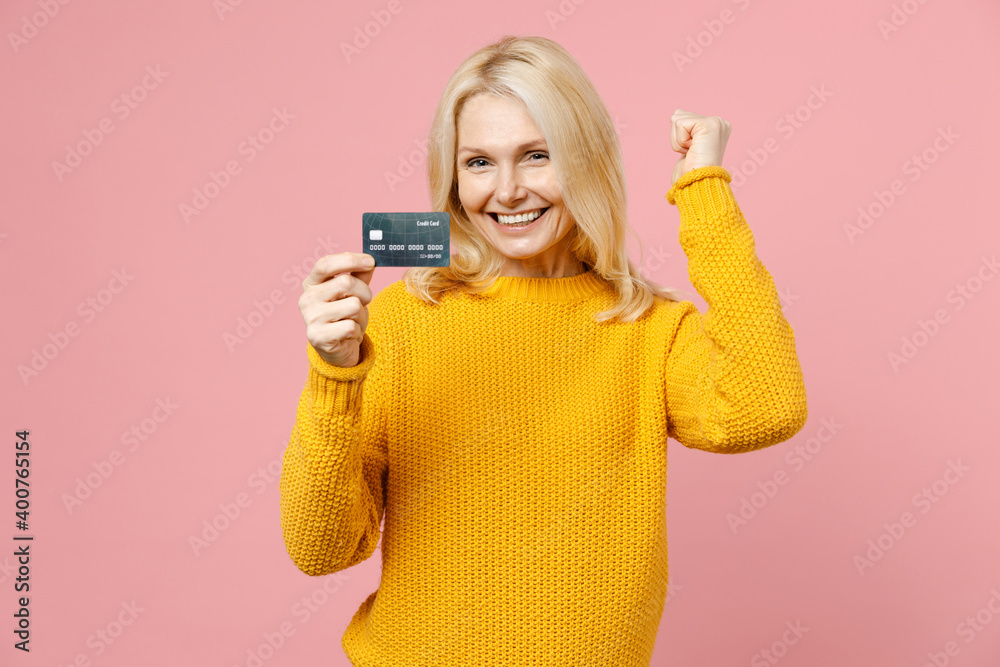 Fototapeta Happy elderly gray-haired blonde woman lady 40s 50s years old wearing yellow basic sweater standing hold credit bank card doing winner gesture isolated on pastel pink color background studio portrait.