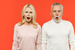 Leinwandbild Motiv Shocked amazed worried couple two friends elderly gray-haired man blonde woman in white pink casual clothes standing keeping mouth open looking camera isolated on orange background studio portrait.