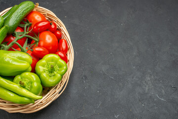 Fresh vegetables red tomatoes with stems green peppers and cucumbers necessary for cooking on dark background