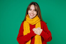 Smiling Pleasant Young Brunette Woman 20s In Basic Casual Knitted Red Sweater Yellow Scarf Standing Holding Hands On Heart Looking Camera Isolated On Bright Green Color Background Studio Portrait.
