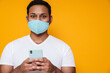 Asian man in face mask using mobile phone and looking at camera