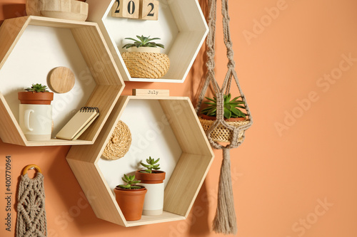 Shelves with decorative elements on color wall. Space for text
