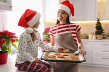 Mother Giving Her Cute Little Daughter Freshly Baked Christmas Cookies In Kitchen