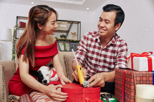 Photo Pretty smiling young woman with dog on her laps helping husband with wrapping an