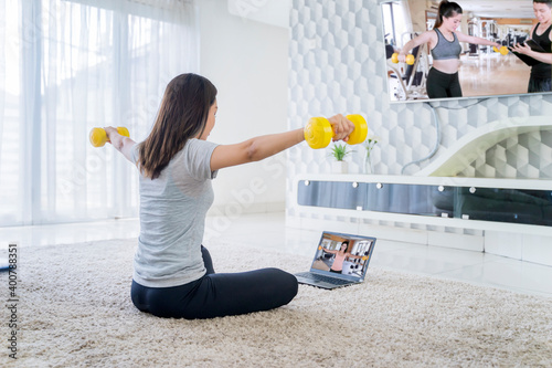 Woman exercising while looking trainer on laptop Wallpaper Mural