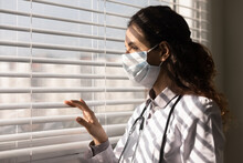 Close Up Of Female Doctor In Facial Mask Against Corona Virus Look In Distance Thinking Or Pondering. Woman GP In Medical Facemask From Covid-19 Pandemics, Dream Or Plan Future Opportunities.