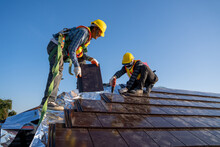 Two Work Construction Worker Wearing Safety Height Equipment Harness Belt During Working And Install New Ceramic Tile Roof With Roofing Tools Electric Drill Used In The Construction Site.