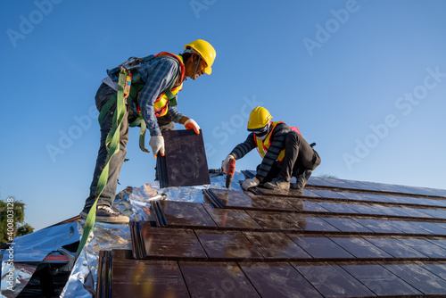 Stampa su Tela Two work construction worker wearing safety height equipment harness belt during working and install new ceramic tile roof with Roofing tools electric drill used in the construction site