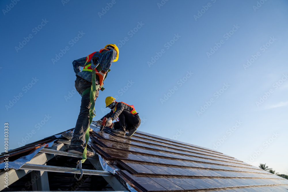 Fototapeta Construction worker wearing safety height equipment harness belt during working install new ceramic tile roof of building with Roofing tools electric drill used in the construction site.