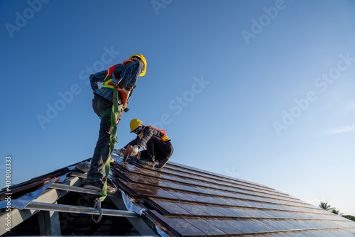 Fotografie, Obraz Construction worker wearing safety height equipment harness belt during working install new ceramic tile roof of building with Roofing tools electric drill used in the construction site