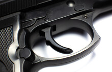 Trigger Of A Black Gun, Pistol Lies On A White Background. Close Up.