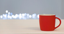 Empty Red Cup With Free Space For Text Or Emblem With Bokeh Lights On Background. Banner For Coffee House, Barista Or Winter Drink Blank With Copy Space.