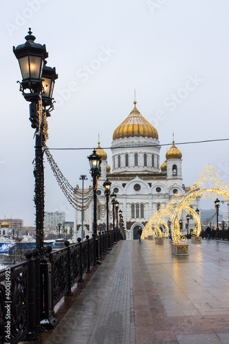 Moscow, Russia, December, 20, 2020: View of the white Cathedral of Christ the Saviour and the bridge with Christmas decorations on a cloudy winter day and space for copying © Inna Polekhina