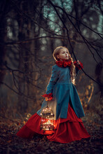 Beautiful Girl With Glowing Cage In Dark Autumn Forest