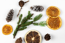 Cones And Spruce Branches With Dry Slices Of Citrus On A White Background. Concept Of New Year Celebration