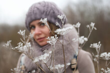 A Woman In Winter Clothes Walks In The Park. Around The Dried Plants Covered With Ice Crust And Frost. The Woman Is Out Of Focus.