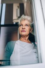 View Of Senior Woman Through Window