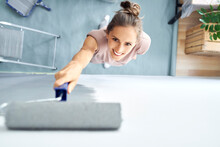 Smiling Young Woman Painting Wall With Paint Roller While Standing At Home