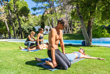 Message Therapists Treating Tourists Lying On Grass At Health Spa During Sunny Day