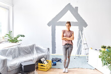 Young Woman With Arms Crossed Standing Against House Painted On Wall At Home