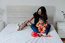 Mother Sitting With Son Weraing Halloween Costume And Dog Lying On Bed At Home