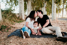 Parents Kissing While Sitting With Baby Bot On Blanket Outdoors