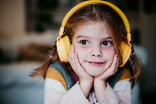Cute Girl With Headphones And Head In Hands Looking Away While Standing At Home