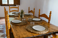 Place Setting On Wooden Dining Table With Empty Chairs In Room