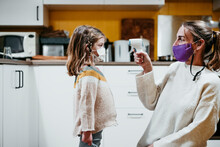 Mother Wearing Face Mask Checking Temperature Of Daughter While Sitting At Home