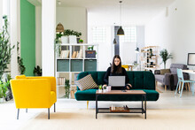 Young Female Influencer Blogging Through Laptop While Sitting On Sofa At Loft Apartment