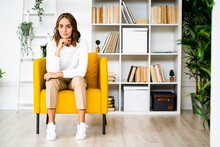 Young Businesswoman Sitting With Head In Hands On Sofa At Office