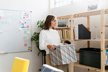 Businesswoman Carrying Box While Setting Up New Office
