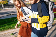 Sibling Holding Hands While Using Smart Phone Walking In Public Park On Sunny Day