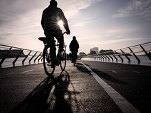 Denmark, Copenhagen, Silhouettes Of Two People Riding Bicycles Across Langebro Bridge At Sunset
